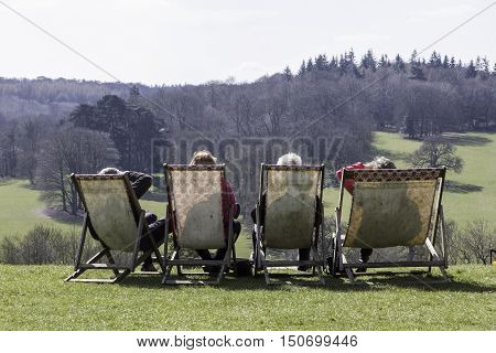 A group of elderly people admire the scenic view from deck chairs on the lawn during a family day out.