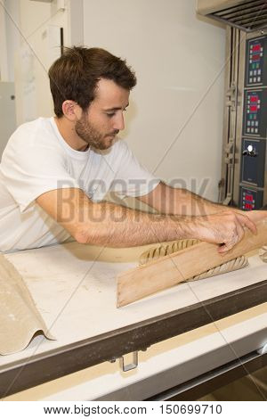 Male baker baking fresh bread in the bakehouse near oven