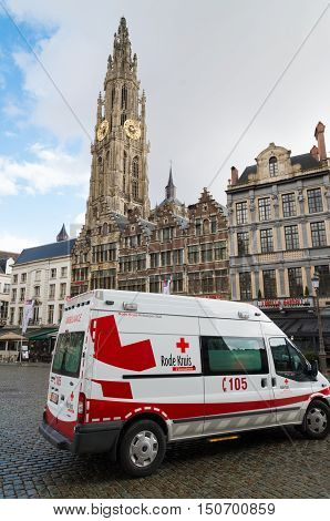 ANTWERP BELGIUM - MARCH 6 2016: Red cross car on the Grote Markt (grand market square) with the onze-lieve-vrouwe cathedral in the background