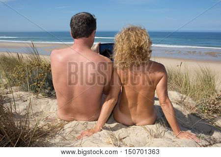 Happy Nudist Couple Sitting On Beach With Tablet