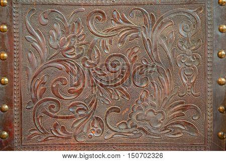 Vintage floral decorative pattern on brown leather