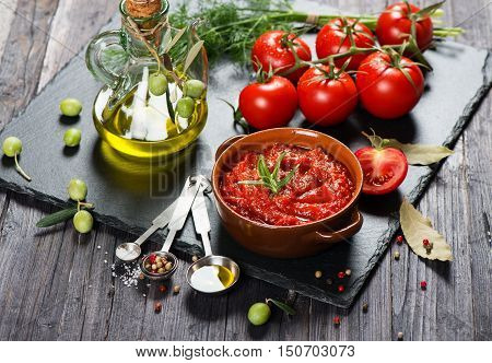Tomato sauce in a ceramic casserole and fresh ingredients ( tomatoes spices olive oil) on a black slate board.