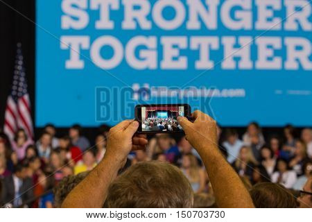 Harrisburg PA USA - October 4 2016: A man uses his smartphone to take a picture of the Smarter Together Sign at the rally for Presidential candidate Hillary Clinton.