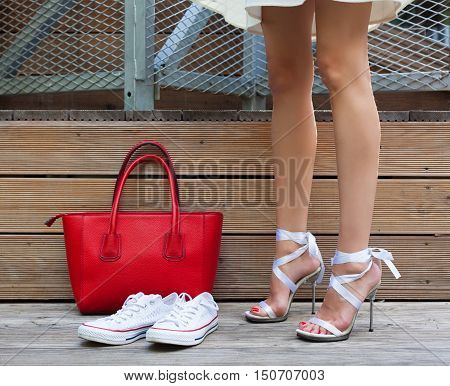 Ribbon Tie Stilleto shoe sneakers and fashionable big red handbag. Fashionable woman with long beautiful legs standing on a wooden background. Part of body.