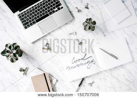 Good morning. Flat lay top view office table desk. Workspace with laptop diary succulent and clips on marble background.