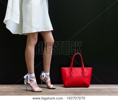 Fashionable woman with long beautiful legs in Ribbon Tie Stilleto shoes standing on the black background. Girl stands next to large red handbag. Part of body. Fashion and Style