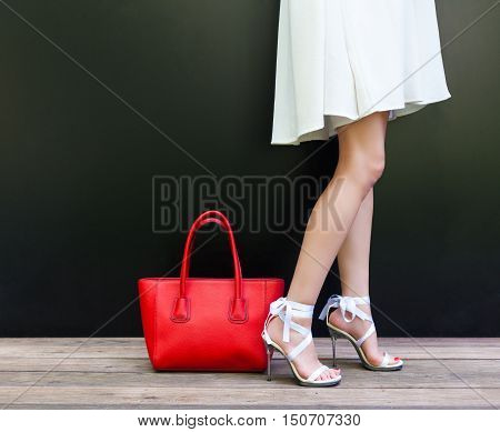 Fashionable woman with long beautiful legs in Ribbon Tie Stilleto shoes standing on the black background. Short white dress. Girl stands next to large red handbag. Part of body. Fashion and Style.