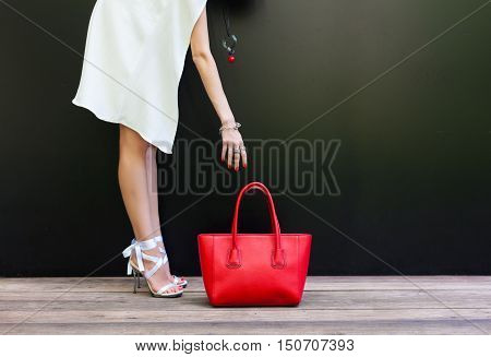 Shopping. Girl pulls her hand to the bag. fashion girl in a short white dress in beautiful shoes with ribbons and large red handbag on a black background. Part of body.