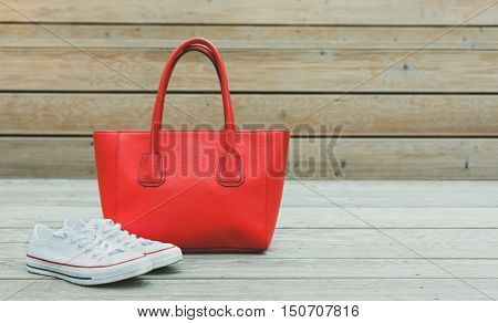 Fashion and Style. Sport. Sneakers and the large red handbag standing on a wooden background.