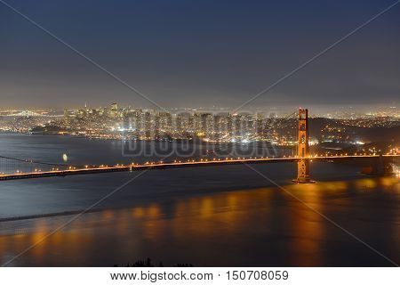 Golden Gate Bridge at night, with San Francisco city skyline at back ground, San Francisco, California, USA.