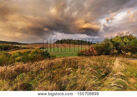 Dense clouds illuminated by the sun and the colorful autumn. Moravian landscape Svitavka.