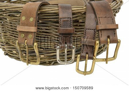 Handmade leather belts with metal buckles  arranged over a hand woven willow basket