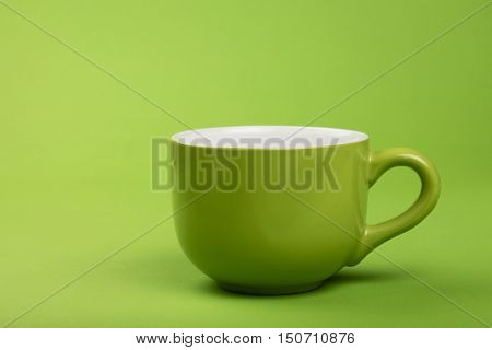 One Full Big Coffee Tea Cup Over Green Paper