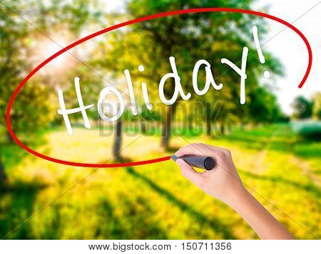 Woman Hand Writing Holiday! With A Marker Over Transparent Board