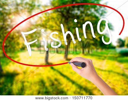 Woman Hand Writing Fishing With A Marker Over Transparent Board