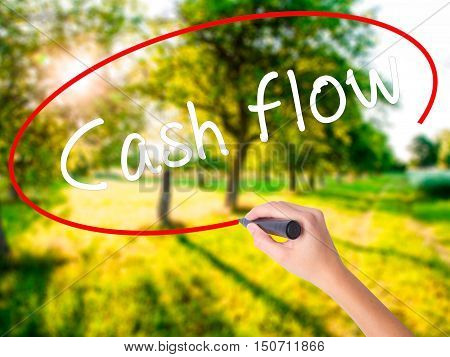 Woman Hand Writing Cash Flow With A Marker Over Transparent Board
