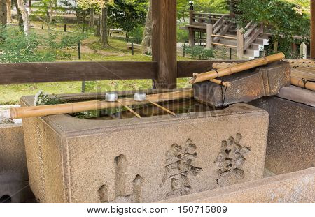 Kyoto Japan - September 15 2016: At the Shinnyo-do Buddhist Temple the large stone Harai hand wash basin offers two cups on a stick. The rinsing is called Temizu. Set in park.