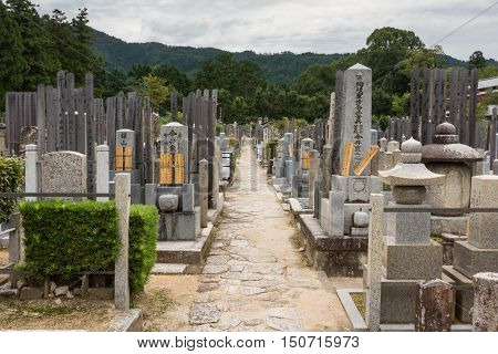 Kyoto Japan - September 15 2016: Adjacent to the Shinnyo-do Buddhist Temple is a large cemetery serving the Buddhist community. Long alley with the classic Japanese tombstones leads to the woods. Mountains in the back.