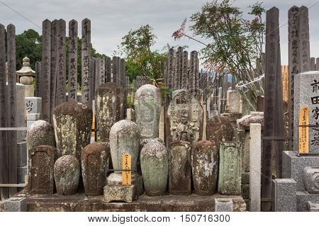Kyoto Japan - September 15 2016: Adjacent to the Shinnyo-do Buddhist Temple is a large cemetery serving the Buddhist community. A group of old cylindrical tombstones are set together.