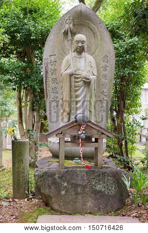 Kyoto Japan - September 15 2016: At the Shinnyo-do Buddhist Temple the stone statue of a Bodhisattva stands in the garden. He is surrounded by green trees and carries a ball and a walking staff.