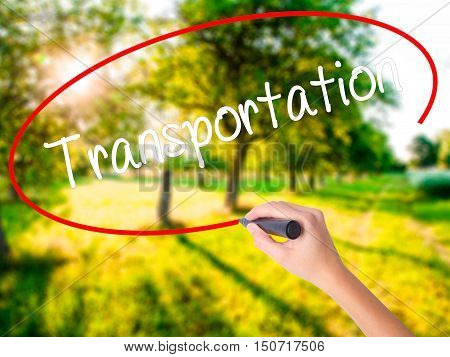 Woman Hand Writing Transportation With A Marker Over Transparent Board .