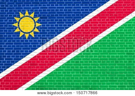 Namibian national official flag. African patriotic symbol banner element background. Flag of Namibia on brick wall texture background, 3d illustration