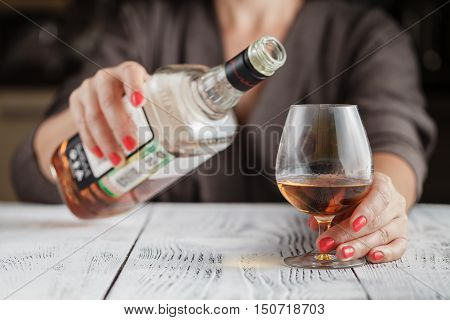 Lonely and thirsty, woman drinks more whiskey