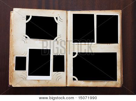 Vintage photo album with blanked photos on old wooden texture