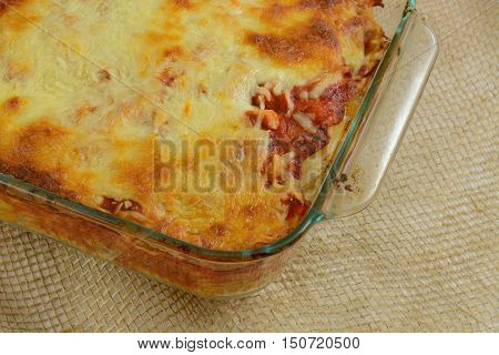 Close up oif Baked casserole with melted cheese, marina sauce, chicken and mixed vegetables on rotini pasta in glass baking dish