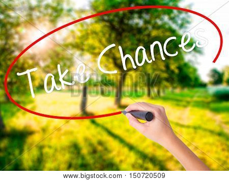 Woman Hand Writing Take Chances With A Marker Over Transparent Board .