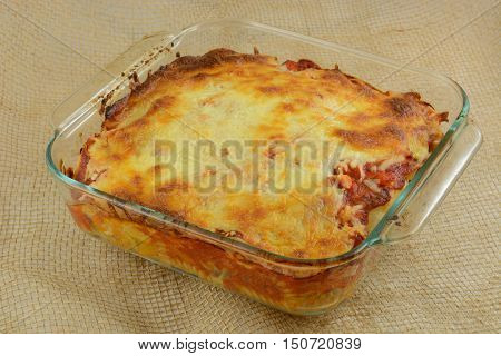 Baked casserole with melted cheese, marina sauce, chicken and mixed vegetables on rotini pasta in glass baking dish