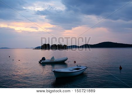 White rowboat and rubber boat with motor at anchor in calm blue sea water inshore after sunset on beautiful evening seascape