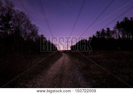 Twilight road stretches toward the horizon beneath power lines
