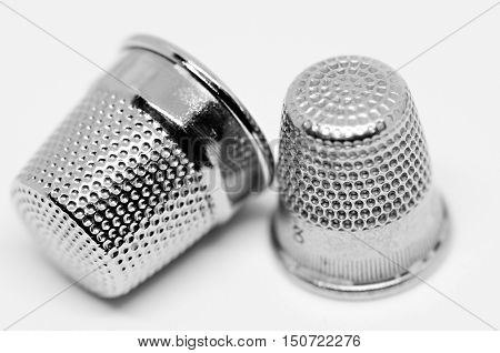 Two old thimbles next to each other.