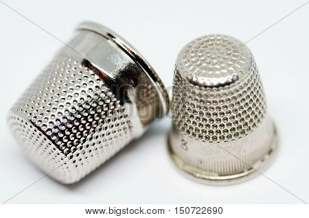 Two old thimbles next to each other