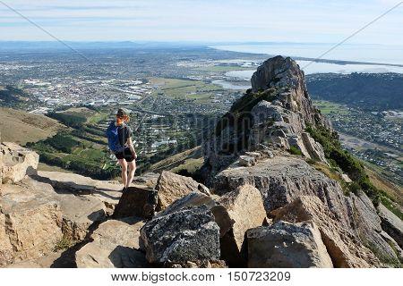 Woman Hiker Ascending Castle Rock.  Port Hills, Christchurch, Canterbury, New Zealand.