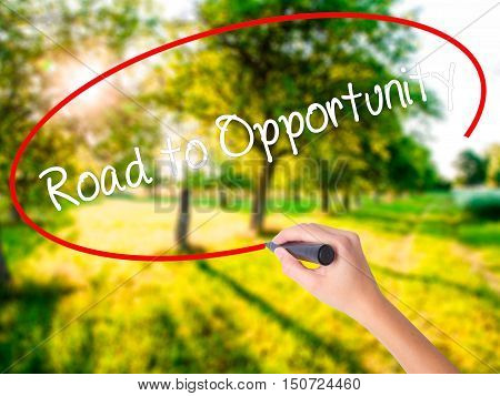 Woman Hand Writing Road To Opportunity With A Marker Over Transparent Board