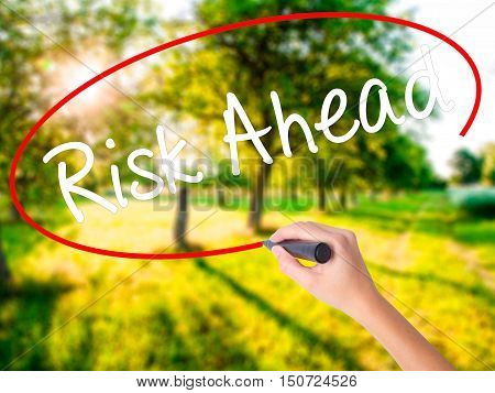 Woman Hand Writing Risk Ahead With A Marker Over Transparent Board