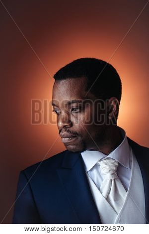 Handsome man african American groom in elegant suit coat with white tie and shirt for wedding ceremony