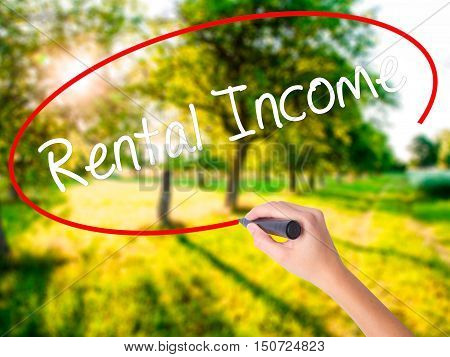 Woman Hand Writing Rental Income With A Marker Over Transparent Board .