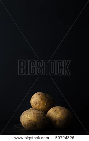 Potatoes Grouped With Soil On Black Slate