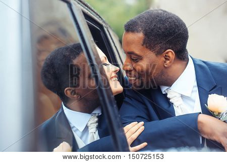 Happy newlyweds of beautiful bride woman in car and african American groom man kiss outdoors on wedding day
