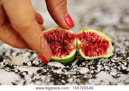 Female fingers with fig fruit with red juicy flesh and green skin cut in at halves on grey background