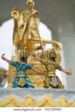 Four Faces Brahma Statue in a Shrine at the village selective focus Thai folk dancer doll