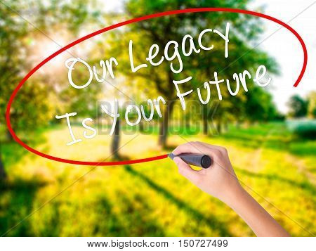 Woman Hand Writing Our Legacy Is Your Future  With A Marker Over Transparent Board