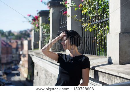 Pretty young beautiful woman with short brunette hair in casual wear outdoors on sunny summer day on streetscape