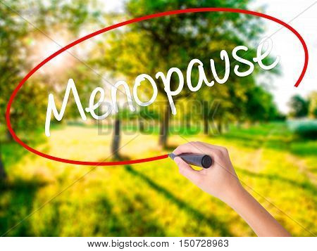 Woman Hand Writing Menopause With A Marker Over Transparent Board .