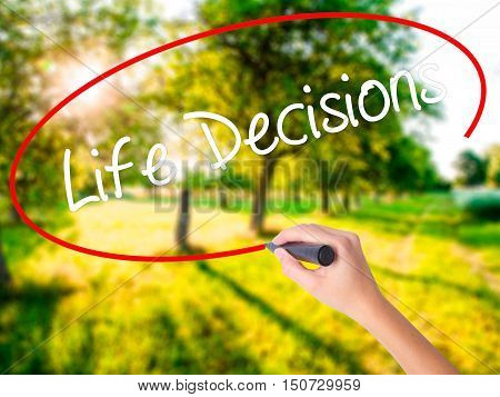 Woman Hand Writing Life Decisions With A Marker Over Transparent Board .