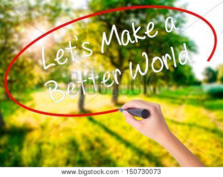 Woman Hand Writing Let's Make A Better World With A Marker Over Transparent Board