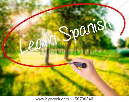 Woman Hand Writing Learn Spanish With A Marker Over Transparent Board